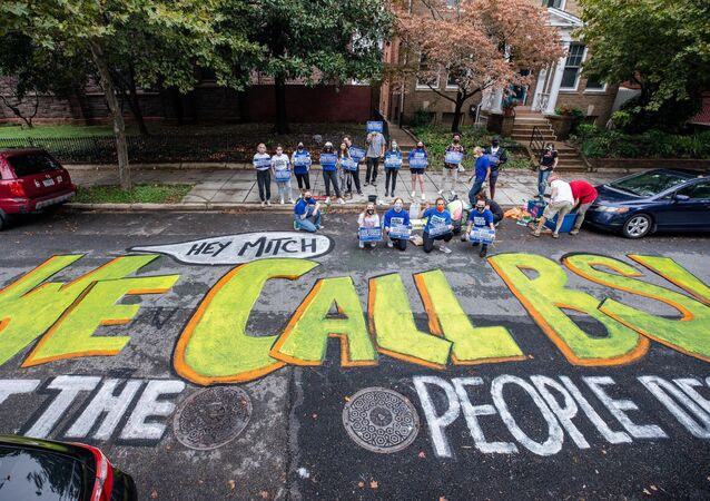 Youth activists with March For Our Lives movement hold signs after painting a mural outside Senate Majority Leader Mitch McConnell's residence in Washington, DC, United States, on 26.09.2020.