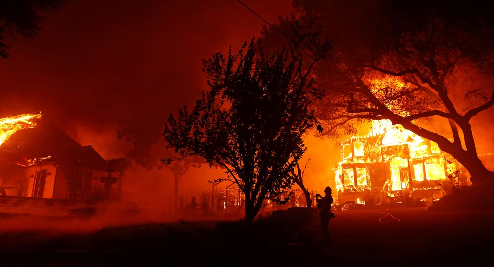 A photographer films a burning property during the Glass Fire in St. Helena, California, U.S. September 27, 2020.