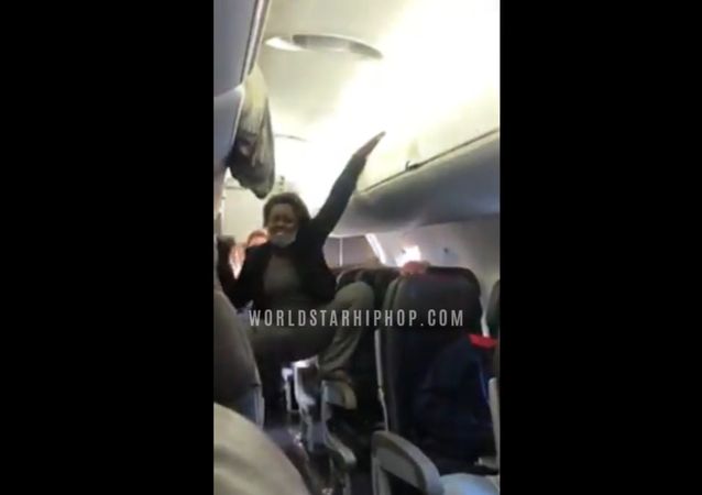 Woman climbs on seats and threatens passengers.