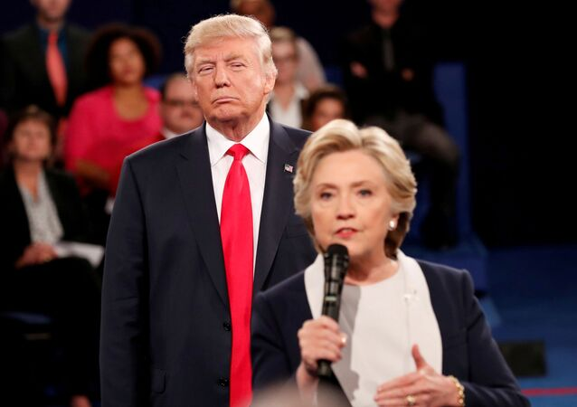 FILE PHOTO: Republican US presidential nominee Donald Trump listens as Democratic nominee Hillary Clinton answers a question from the audience during their presidential town hall debate at Washington University in St. Louis, Missouri, US, 9 October 2016