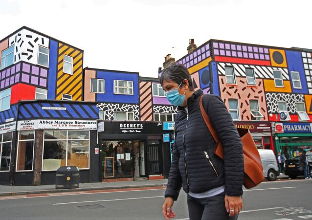 A woman wearing a face mask walks past shops and a mural created by artist Camille Walala, amid the spread of the coronavirus disease (COVID-19), in Leyton, London, Britain, September 29, 2020