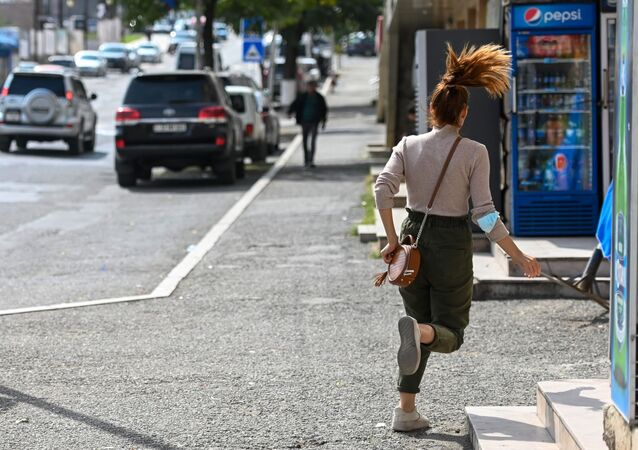 A young woman runs down a street in Stepanakert