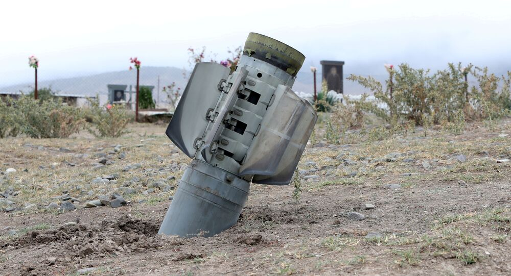 The remains of a rocket shell are seen near a graveyard in the town of Ivanyan (Khojaly) in the breakaway region of Nagorno-Karabakh, October 1, 2020