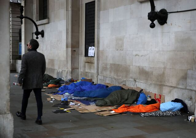 A man walks past homeless people sleeping under the portico of St Paul's Church in Covent Garden, London