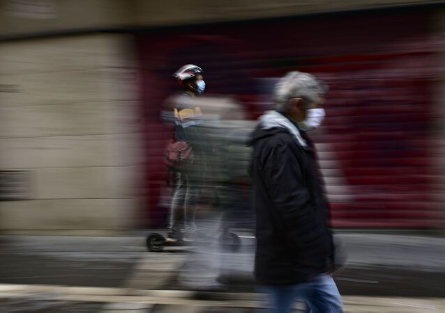 A man using an e-scooter rides past an old man wearing a face mask in Pamplona, northern Spain.