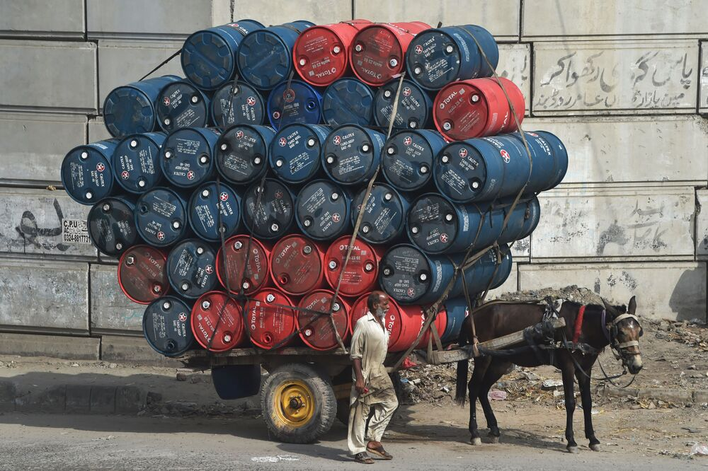 A man stands next to a horsecart laden with oil drums on a street in Lahore on 27 September 2020.