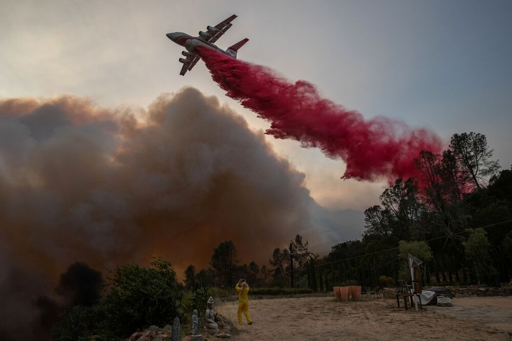 A woman wearing flame-resistant clothing photographs an airplane as it drops red fire retardant on the Glass Fire at a vineyard in Deer Park, California, US, 27 September 2020.