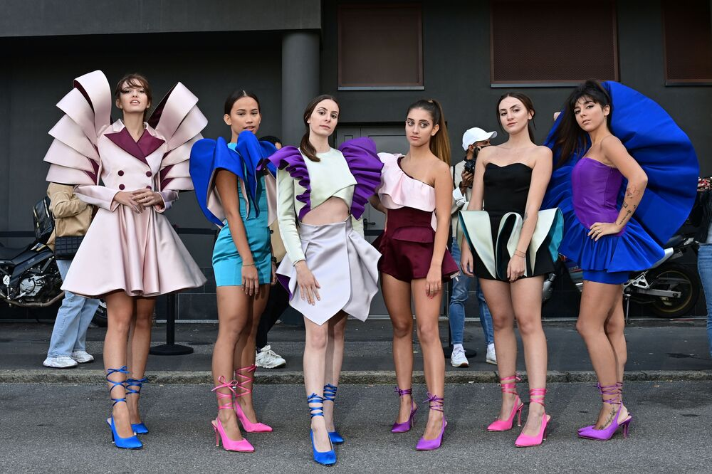 Nora Bourelly, right, and other former students of the Istituto Marangoni (Marangoni Fashion Institute) in Milan pay scant regard to COVID-19 restrictions as they show off Bourelly's creations in a street outside Valentino's Spring/Summer 2021 women's and men's show, during Milan Fashion Week on 27 September 2020.