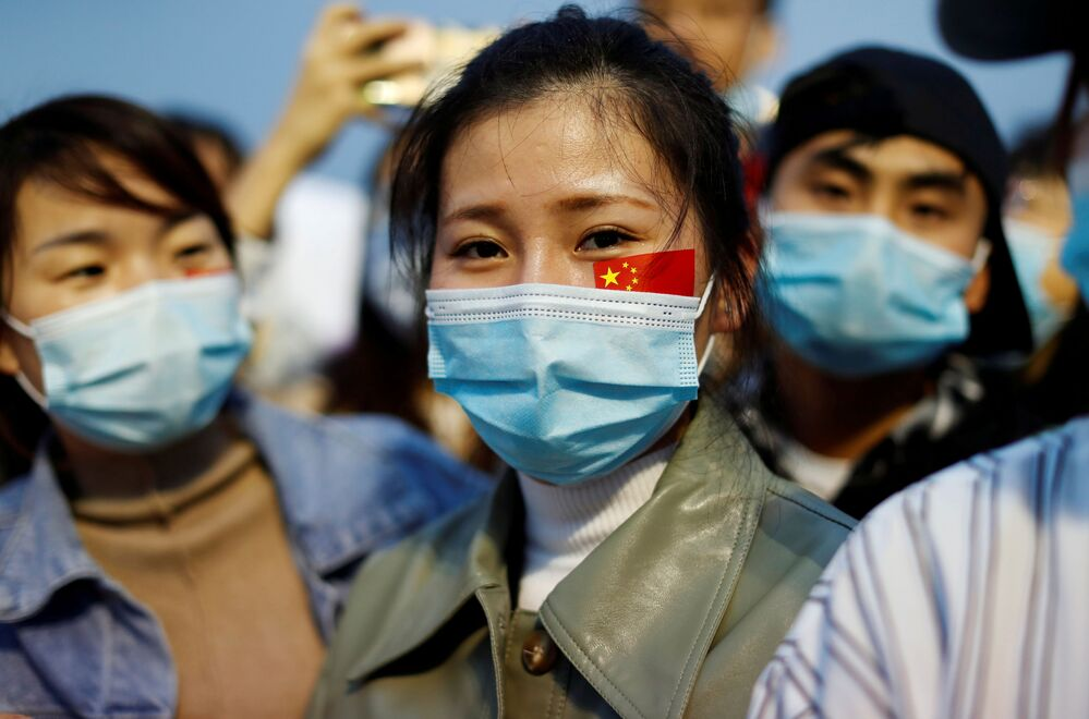 People wearing face masks, after the coronavirus disease (COVID-19) outbreak, attend a flag-raising ceremony at Tiananmen Square on National Day to mark the 71st anniversary of the founding of People's Republic of China, in Beijing, China 1 October 2020.