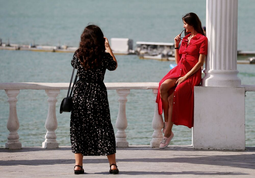 Young women pose for a picture at Lake Abrau in Russia's Krasnodar territory.