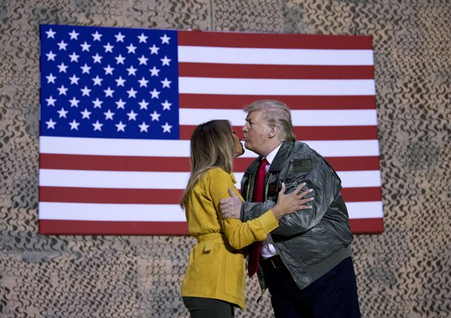 President Donald Trump kisses first lady Melania Trump during a hangar rally at Al Asad Air Base, Iraq, Wednesday, Dec. 26, 2018. President Donald Trump, who is visiting Iraq, says he has 'no plans at all' to remove U.S. troops from the country