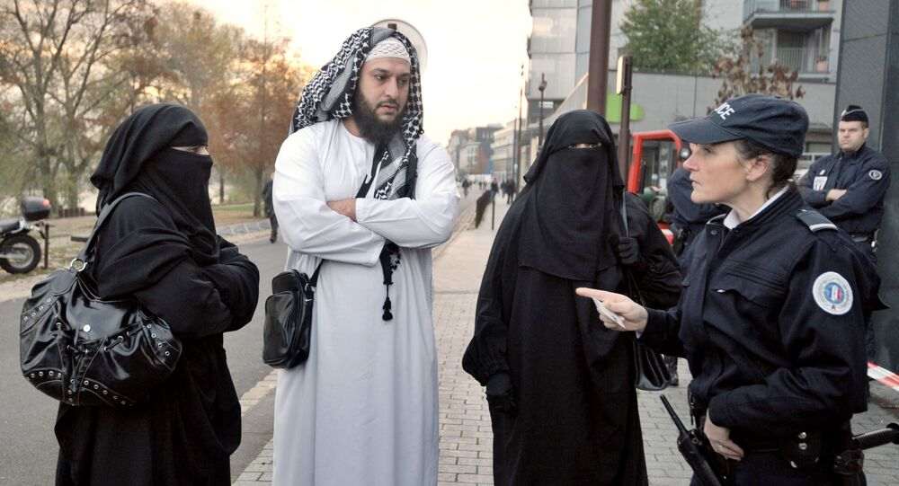 A police woman carries out an identity check of a wife  wearing a full-face veil of French owner of a chain of butcher's and grocery shops, Lies Hebbadj (C), outside the court of justice where she was to appear because she violated France's niqab ban, on November 21, 2011 in the French western city of Nantes