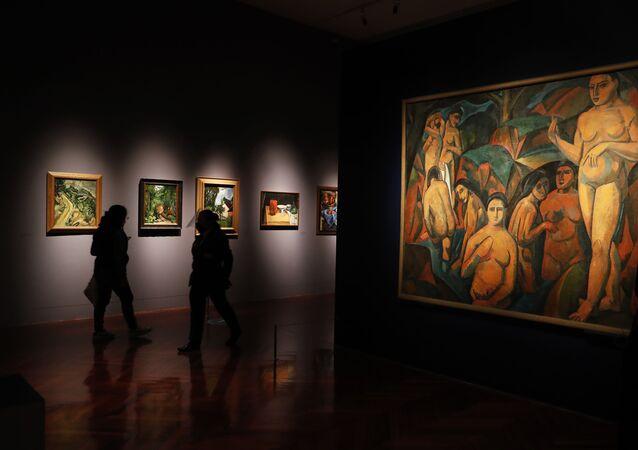 Journalists walk past a painting by Andre Derain, left, during the El Paris de Modigliani y sus Contemporáneos or The Paris of Modigliani and his contemporaries exhibit at the Palacio de Bellas Artes in Mexico City, Monday, Sept. 7, 2020.