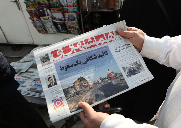 An Iranian holds a newspaper with a picture of the debris of the Ukrainian plane that crashed in Tehran earlier this week, outside a news stand in the Islamic republic's capital on January 11, 2020.