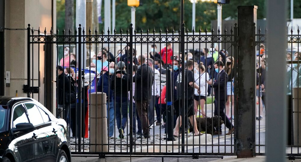 A crowd of members of the public gathers outside the gates of Walter Reed National Military Medical Center as the Marine One helicopter with U.S. President Donald Trump aboard