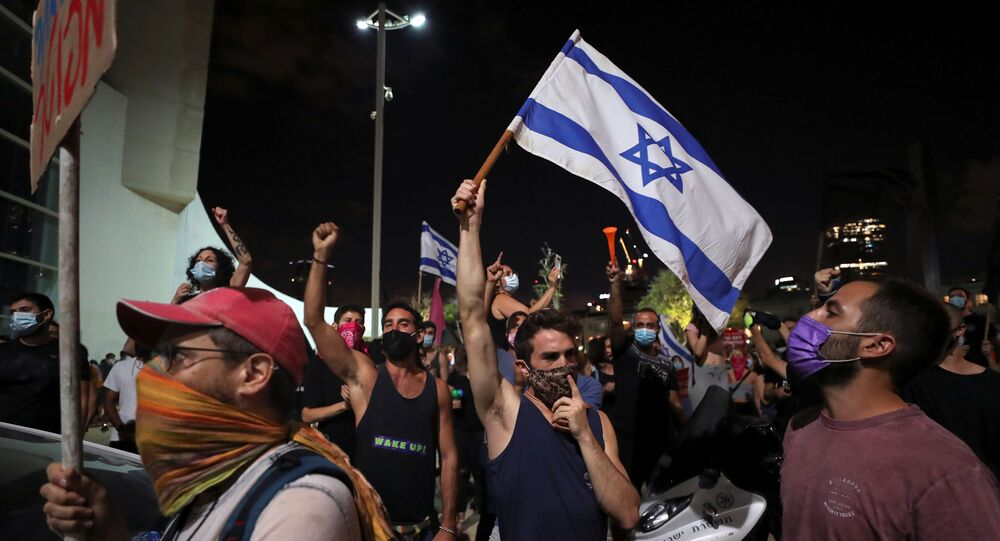 Israelis protest against legislation banning them from holding demonstrations more than 1 km (0.6 miles) from their homes, a measure the government said was aimed at curbing the coronavirus disease (COVID-19) infections, in Tel Aviv, Israel October 3, 2020.