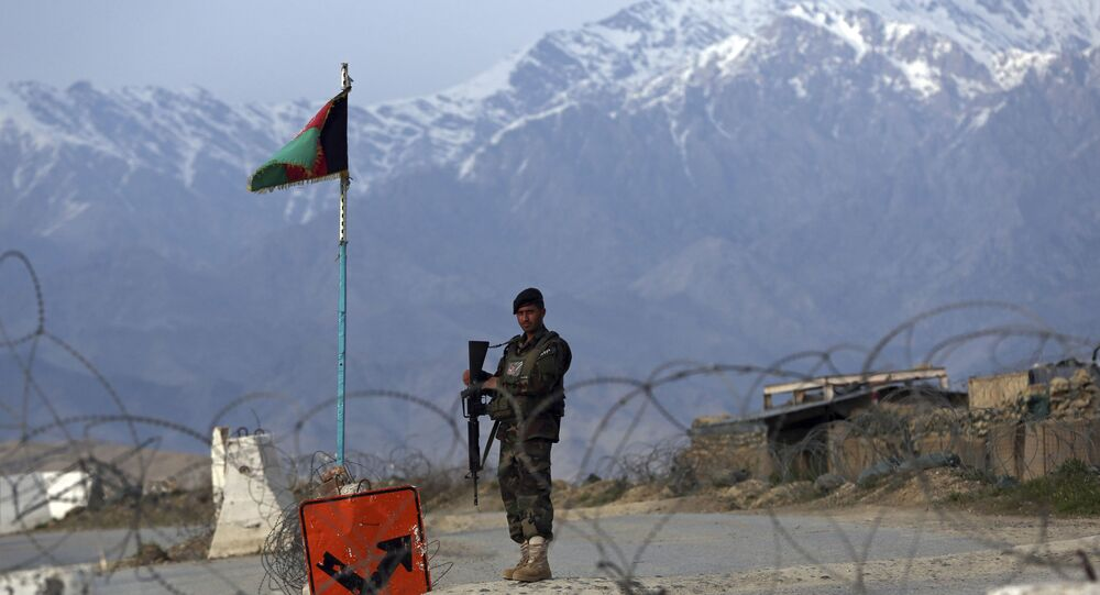 In this Wednesday, April 8, 2020, file photo, an Afghan National Army soldier stands guard at a checkpoint near the Bagram base north of Kabul, Afghanistan.
