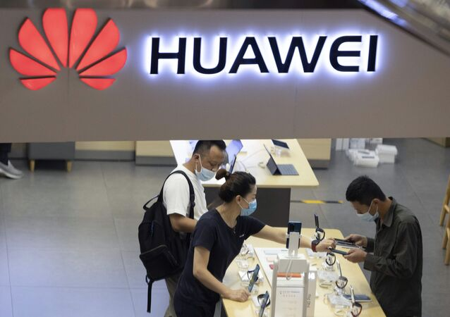 In this July 15, 2020, file photo, visitors wearing masks to curb the spread of the coronavirus look at the latest products at a Huawei store in Beijing. China accused Washington of damaging global trade with sanctions that threaten to cripple tech giant Huawei and said Tuesday it will protect Chinese companies but gave no indication of possible retaliation