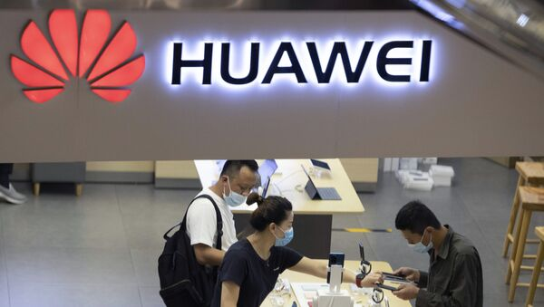 In this July 15, 2020, file photo, visitors wearing masks to curb the spread of the coronavirus look at the latest products at a Huawei store in Beijing. China accused Washington of damaging global trade with sanctions that threaten to cripple tech giant Huawei and said Tuesday it will protect Chinese companies but gave no indication of possible retaliation - Sputnik International