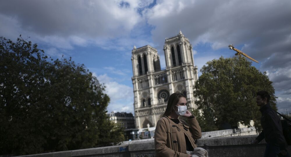 A woman walks by Notre Dame cathedral Saturday Sept.26, 2020 in Paris. While France suffered testing shortages early in the pandemic, ramped-up testing since this summer has helped authorities track a rising tide of infections across the country.