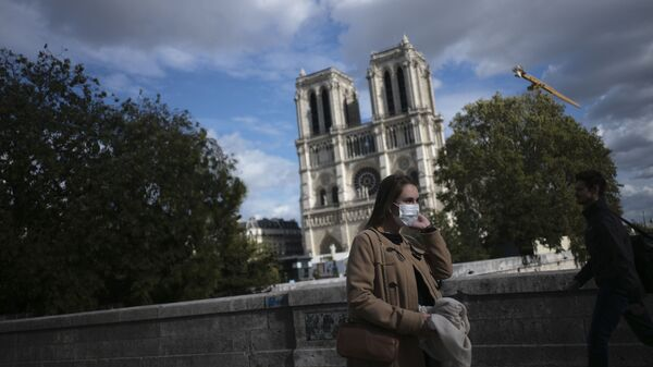 A woman walks by Notre Dame cathedral Saturday Sept.26, 2020 in Paris. While France suffered testing shortages early in the pandemic, ramped-up testing since this summer has helped authorities track a rising tide of infections across the country. - Sputnik International