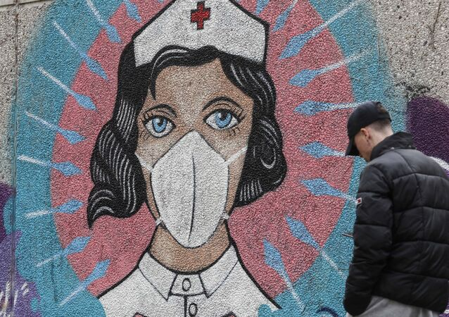 A man passes a graffiti by street artist 'Uzey', depicting a nurse as superhero in the coronavirus pandemic on a wall in Hamm, Germany, Monday, Sept. 28, 2020.