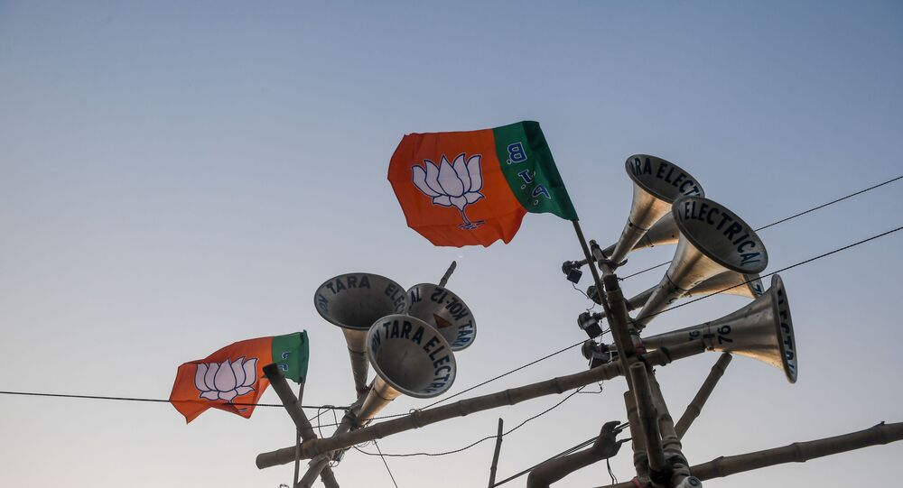 A worker ties a Bharatiya Janata Party (BJP) flag on a structure bearing loudspeakers to prepare for the next day the political rally of Home Minister Amit Shah, in Kolkata on February 29, 2020.