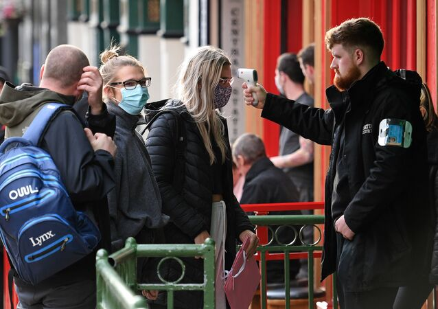 A security guard uses a handheld thermometer to take the temperature of customers, wearing face masks or coverings due to the COVID-19 pandemic, as they wait to enter a bar in Liverpool, north west England on October 2, 2020, following the  announcement of new local restrictions for certain areas in the northwest of the country, due to a resurgence of novel coronavirus cases. - The British government on Thursday extended lockdowns to Liverpool and several other towns in northern England, effectively putting more than a quarter of the country under tighter coronavirus restrictions. Health Secretary Matt Hancock said limits on social gatherings would be extended to the Liverpool City region, which has a population of about 1.5 million. (Photo by Oli SCARFF / AFP)