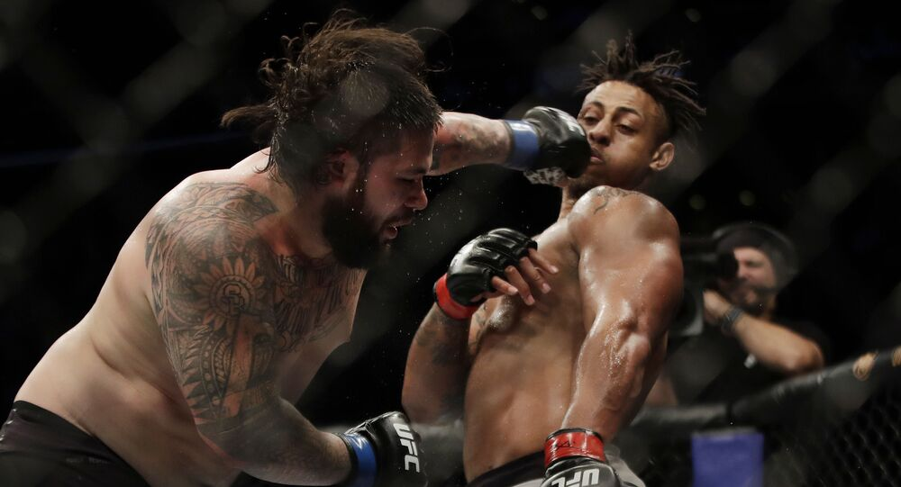 Ben Sosoli, left, lands a punch to Greg Hardy during a heavyweight mixed martial arts bout Friday, Oct. 18, 2019, at UFC Fight Night in Boston