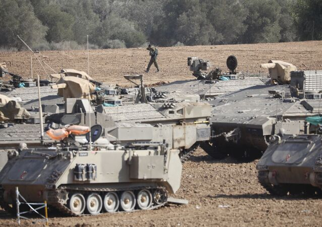 An Israeli soldier walks past military vehicles in a gathering point near the Israel-Gaza Border, Thursday, Nov. 14, 2019