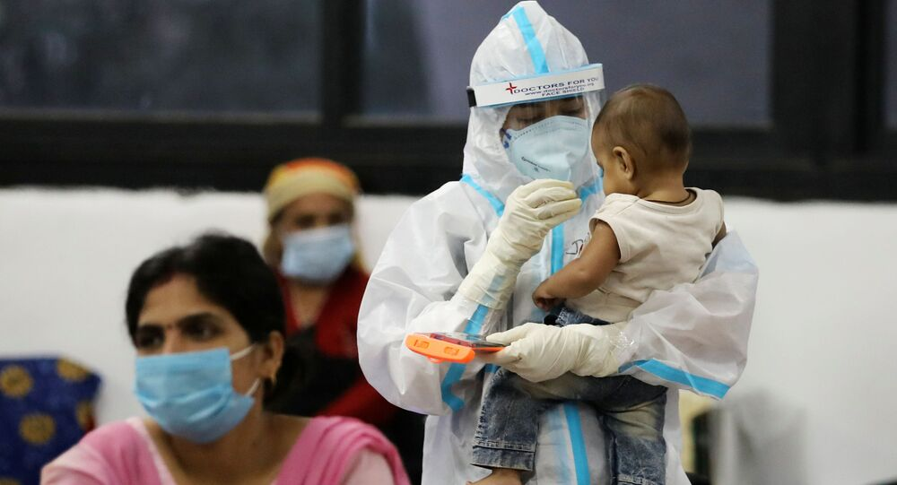 A medical worker in personal protective equipment (PPE) plays with a child of woman recovering inside a quarantine centre for the coronavirus disease (COVID-19) patients amidst the spread of the disease at an indoor sports complex in New Delhi, India, September 22, 2020