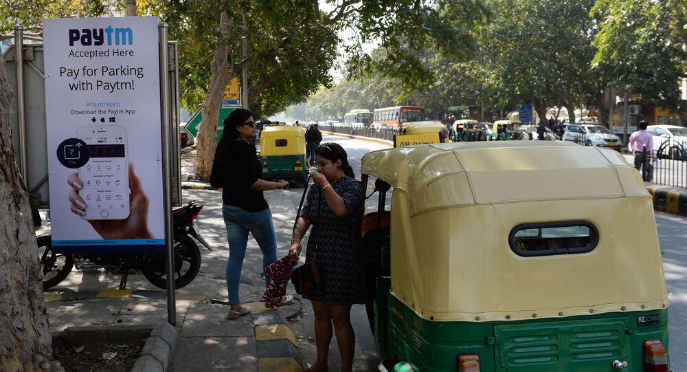 In this photograph taken on February 27, 2017, Indian pedestrians walk past a sign advertising Indian electronic and cellphone-based payment system Paytm outside a parking area in New Delhi
