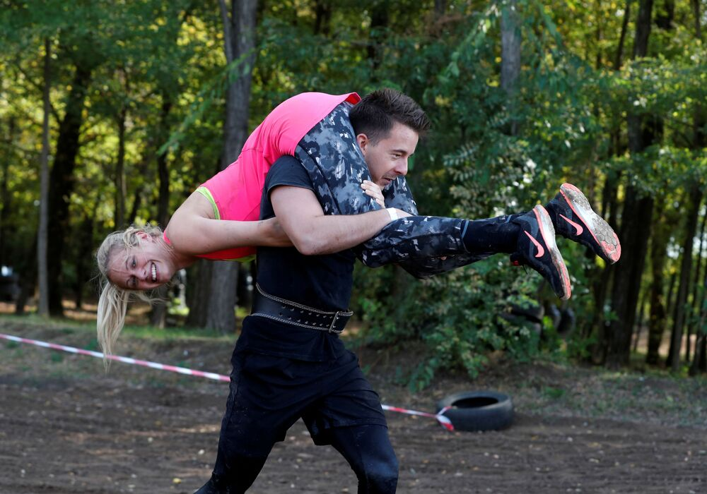 Participants compete in Hungary's first wife-carrying championship in Tapiobicske, Hungary, 3 October 2020.