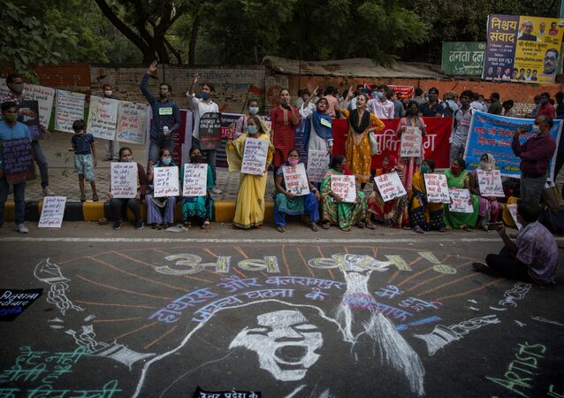 Indians shout slogans and hold placards during a protest condemning the alleged gang rape and killing of a Dalit woman, in New Delhi, India, Sunday, Oct. 4, 2020