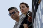 In this May 23, 2019, file photo, Cristiano Ronaldo, left, is flanked by his partner Georgina Rodriguez as they watch the second practice session for a Formula One race at the Monaco racetrack, in Monaco