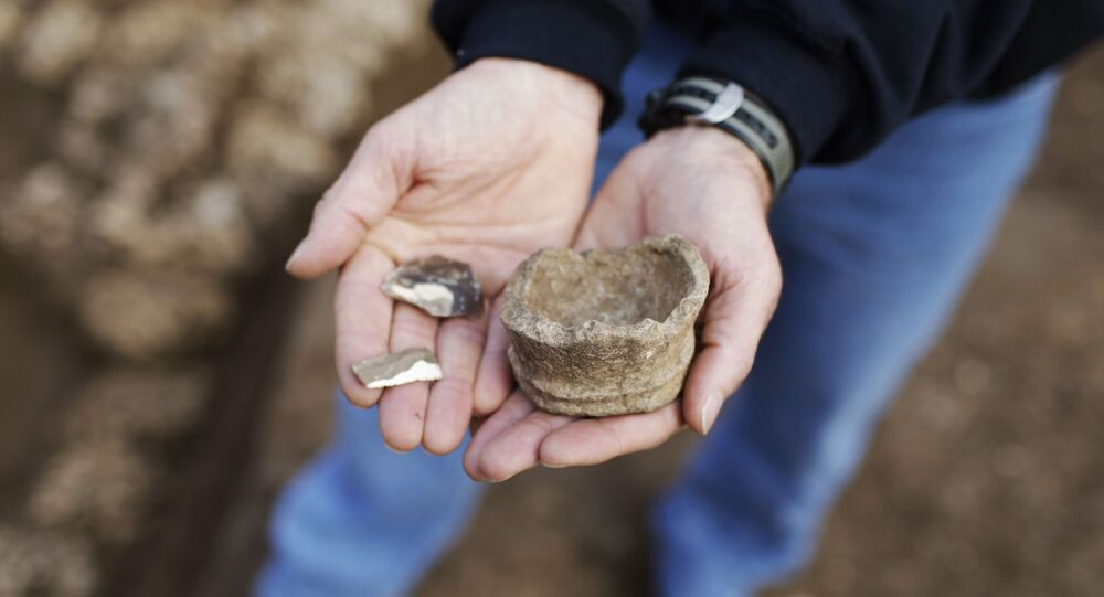 Yoav Arbel of Israel's Antiquities Authority holds pieces of stone artifacts at the excavation site of the Neolithic period in Tel Aviv, Israel, Jan. 11, 2010. Israel's Antiquities Authority say the remains of a prehistoric building as well as ancient flint tools have been discovered in the modern city of Tel Aviv