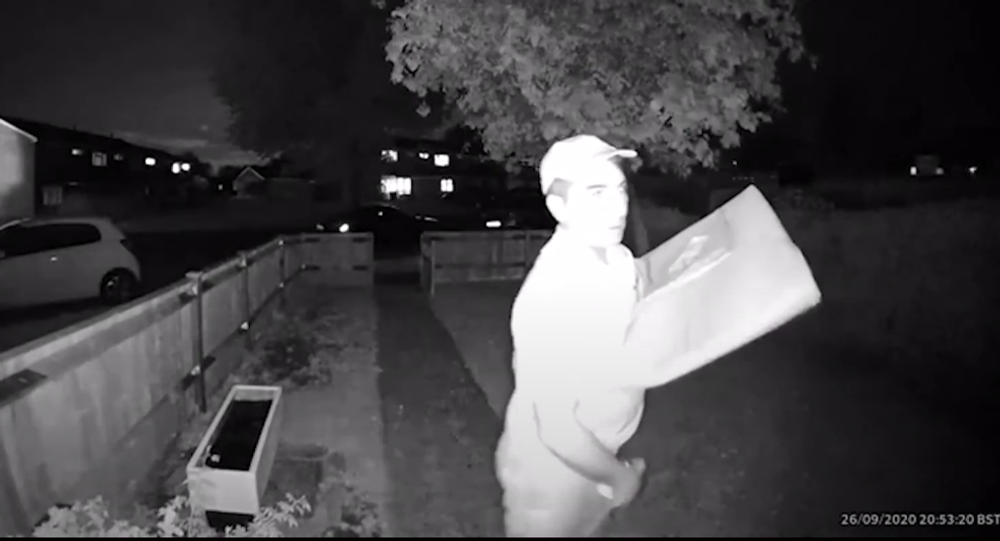 A screenshot from surveillance camera footage of a Domino's Pizza delivery driver rubbing an ice cream container on his crotch while waiting for a customer to open the door.