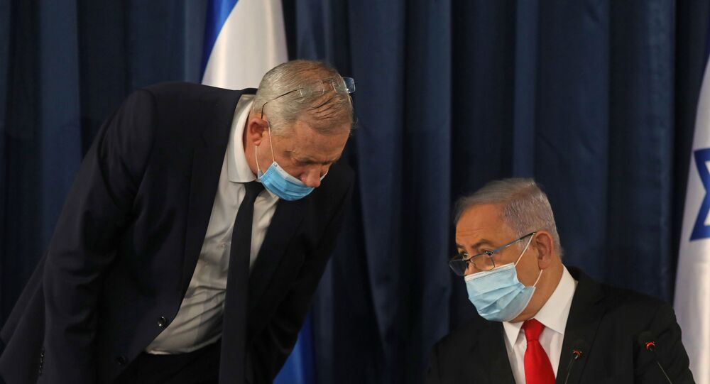 Israeli Prime Minister Benjamin Netanyahu (R) speaks with Alternate PM and Defence Minister Benny Gantz, both wearing protective mask due to the ongoing COVID-19 pandemic, during the weekly cabinet meeting in Jerusalem on June 7, 2020.
