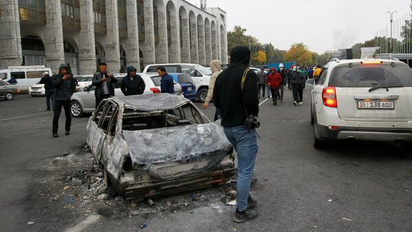 People are seen next to a car burnt during a protest against the results of a parliamentary election in Bishkek, Kyrgyzstan, October 6, 2020 - Sputnik International