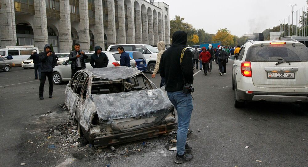 People are seen next to a car burnt during a protest against the results of a parliamentary election in Bishkek, Kyrgyzstan, October 6, 2020