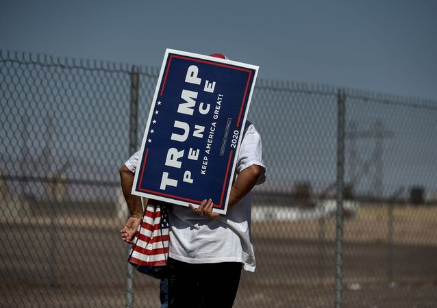A woman holds a Trump Pence sign as she waits in line to attend the Great American Comeback Event campaign rally with US President Donald Trump at Xtreme Manufacturing in Henderson, Nevada on September 13, 2020
