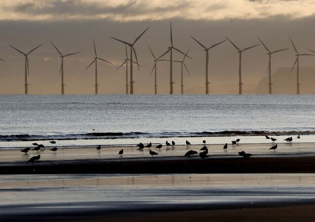 An offshore wind farm is visible from the beach in Hartlepool, England.