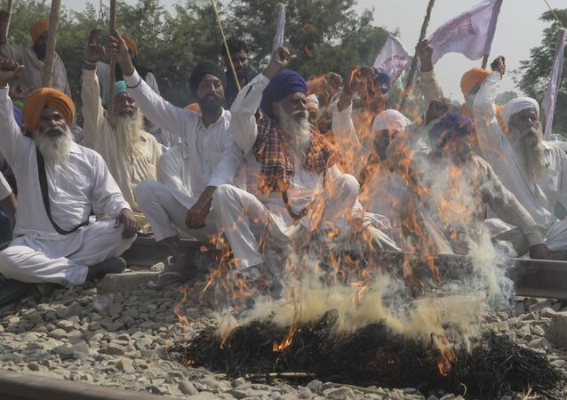 Farmers shout slogans while burning an effigy with pictures of Congress party leader Rahul Gandhi, Indian Prime Minister Narendra Modi, Aam Aadmi Party (AAP) and Member of Parliament Bhagwant Mann and Shiromani Akali Dal (SAD) party President Sukhbir Singh Badal during a protest against the recent passing of agriculture reform bills in the Parliament, on the outskirts of Amritsar on October 6, 2020