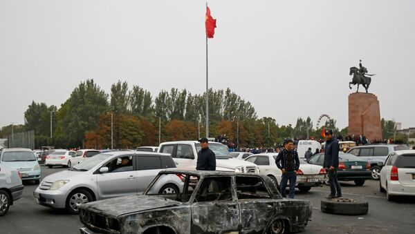 People stand next to a car burnt during a protest against the results of a parliamentary election in Bishkek, Kyrgyzstan, October 6, 2020. - Sputnik International