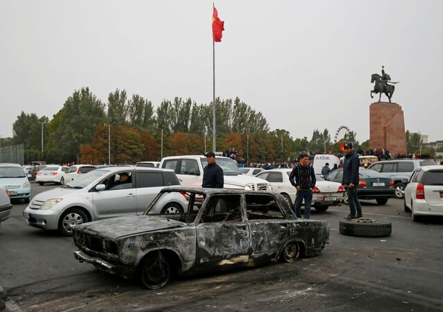 People stand next to a car burnt during a protest against the results of a parliamentary election in Bishkek, Kyrgyzstan, October 6, 2020.