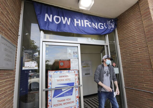 In this Thursday, June 4, 2020 file photo, a customer walks out of a U.S. Post Office branch and under a banner advertising a job opening, in Seattle. The job market took a big step toward healing in May 2020, though plenty of damage remains, as a record level of hiring followed record layoffs in March and April. The Labor Department reported Tuesday, July 7, 2020 that the number of available jobs rose sharply as well, but remained far below pre-pandemic levels.