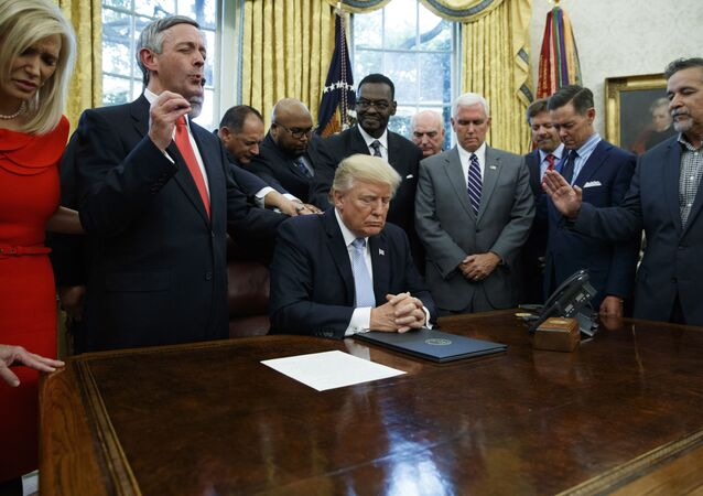 In this Sept. 1, 2017 file photo, religious leaders pray with President Donald Trump after he signed a proclamation for a national day of prayer to occur on Sunday, Sept. 3, 2017, in the Oval Office of the White House in Washington.