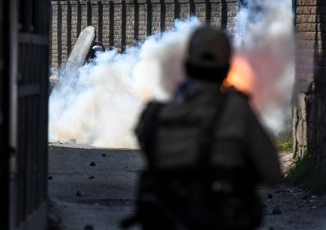 A security personnel (R) fires tear gas towards protesters during clashes with government forces in Batamaloo area of Srinagar on September 17, 2020.