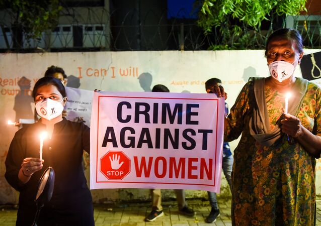 Lawyers display a placard to condemn the alleged gang-rape and murder of a low-caste teenaged woman in Uttar Pradesh state during a candlelight vigil in Ahmedabad on October 6, 2020.