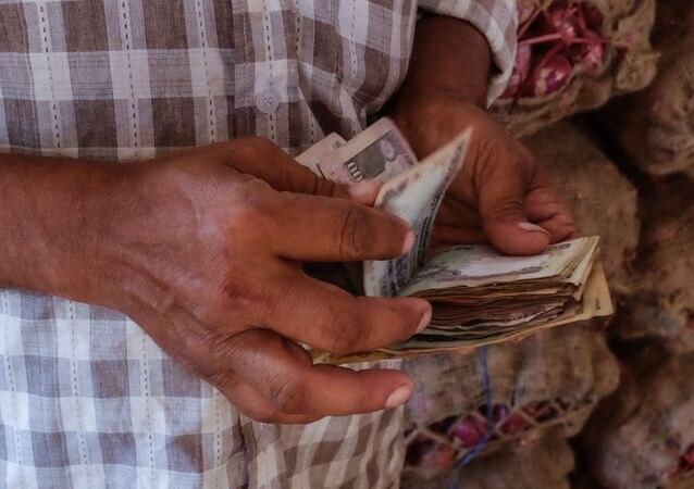 An Indian man counts his money as he pays for a 60 kilo sack of onions at a local market in south New Delhi on September 9, 2015.